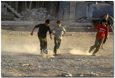 Three boys playing football dusty